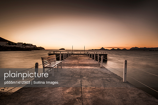 Stone walkway and ocean waves under sunset sky - p555m1412903 by Sollina Images
