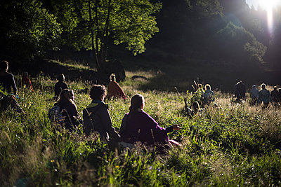 People meditating in the grass of a field at sunrise - p1007m1540349 by Tilby Vattard