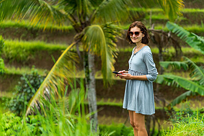 Young lady is ready to take a picture the gorgeous rice fields - p1166m2124293 by Cavan Images