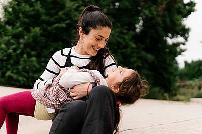 Playful mother and daughter on street during sunny day - p300m2202554 by Ezequiel Giménez