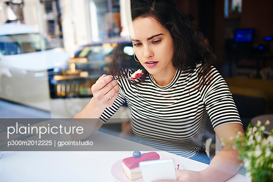 Young woman using cell phone and eating cake at an cafe in the city - p300m2012225 von gpointstudio