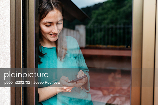 Woman using smartphone at window, man using laptop lying on bed at home - p300m2202732 by Josep Rovirosa