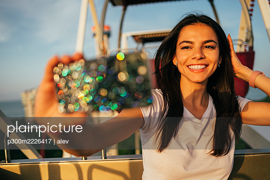 Happy beautiful woman taking selfie with hand in hair on Ferris wheel at amusement park - p300m2226417 by alev
