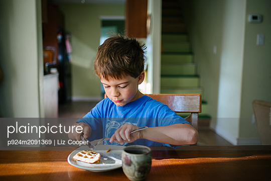 Boy eating waffle breakfast at kitchen table - p924m2091369 by Liz Cooper
