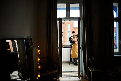 Junges Paar steht auf einem Balkon und umarmt sich glücklich  - p1301m1424725 von Delia Baum