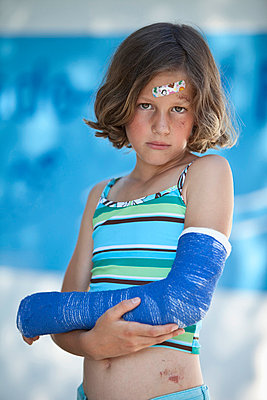 Germany, Bavaria, Wounded girl in swimwear and with broken arm, portrait - p30019975f by Roman Märzinger