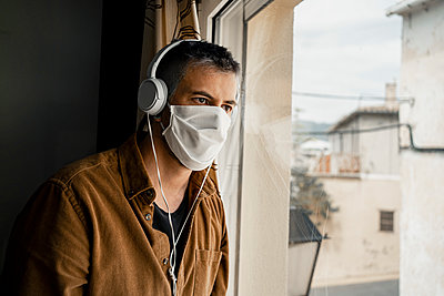 Man wearing protective mask and white headphones looking out of the window - p300m2189084 by Rafa Cortés