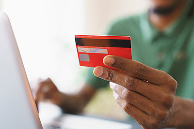 Cropped image of man holding credit while shopping online through laptop at home - p301m1406335 by Halfdark
