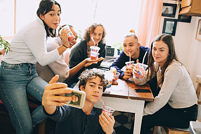 Teenage boy taking selfie with friends through mobile phone while enjoying smoothie at home - p426m2145508 by Maskot