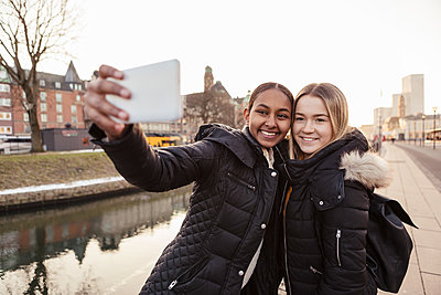 Teenage girl taking selfie with friend on smart phone against canal in city - p426m2149282 by Kentaroo Tryman