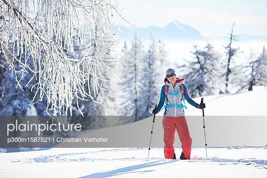 Austria, Tyrol, smiling snowshoe hiker standing in snow - p300m1587521 von Christian Vorhofer