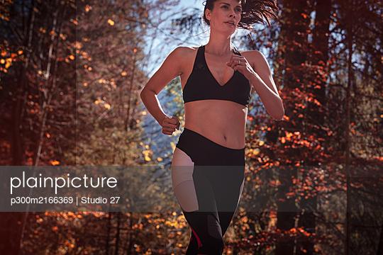 Woman jogging in autumn forest - p300m2166369 von Studio 27