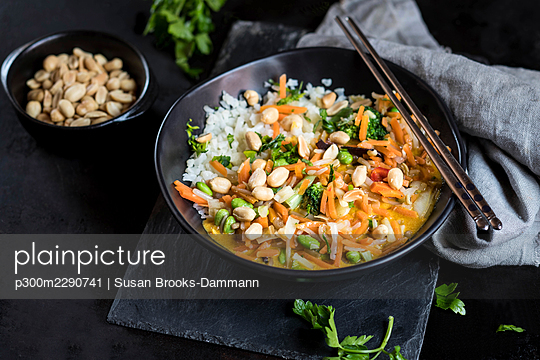 Yellow Thai curry in bowl with steel chopsticks on table - p300m2290741 by Susan Brooks-Dammann
