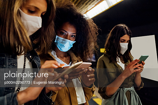 Women with protective face mask using mobile phone while standing in underground - p300m2290773 by Eugenio Marongiu