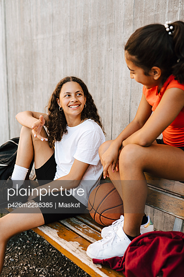 Happy female friends talking with each other at basketball court - p426m2298385 by Maskot
