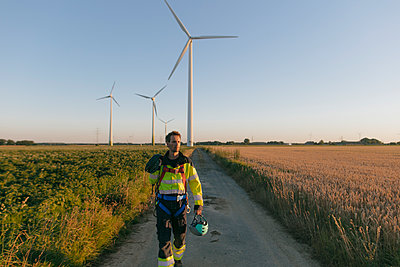 Technician walking on field path at a wind farm with climbing equipment - p300m2058840 von Gustafsson