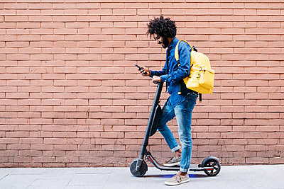 Young man with backpack and E-Scooter standing in front of brick wall looking at cell phone - p300m2114514 by Josep Rovirosa