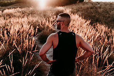 Male sportsperson with hand on hip looking away while standing amidst dried plants during sunset - p300m2251173 by Eva Blanco