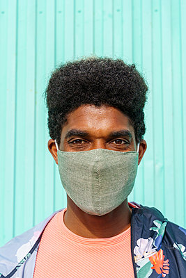 Mid adult man wearing protective face mask in front of turquoise wall - p300m2273512 by VITTA GALLERY