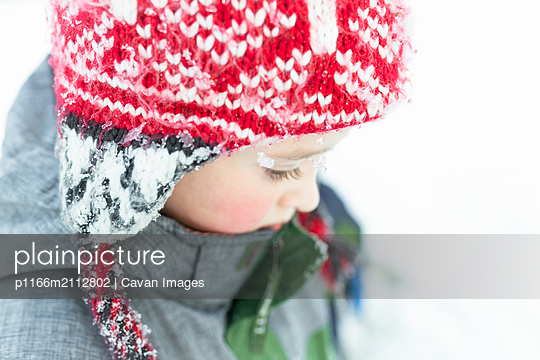 Portrait of elementary age boy wearing red winter hat in the snow - p1166m2112802 by Cavan Images