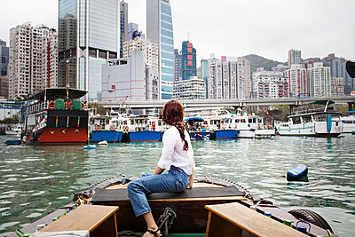 Side view of female tourist looking at buildings by sitting on boat - p1166m1150885 by Cavan Images