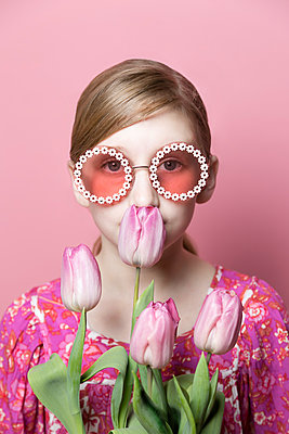 Close up of mod tween girl smelling pink tulips on pink background - p1166m2171547 by Cavan Images