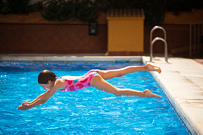 Young girl jumping head first into the pool in summer - p300m2029555 by Javier Sánchez Mingorance