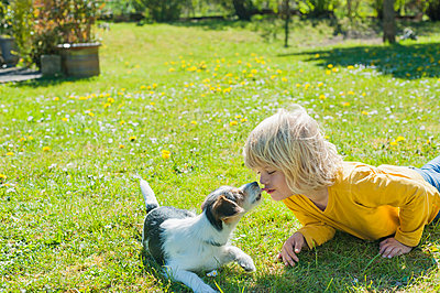 Boy playing with Jack Russel Terrier puppy in garden - p300m940996f by Jana Mänz