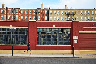 Female jogger running on sidewalk beside paned windows of street side building, Boston, Massachusetts, USA - p343m1500293 by Josh Campbell