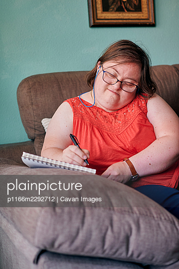 Adult woman with down syndrome writes in a notebook on a couch at home - p1166m2292712 by Cavan Images