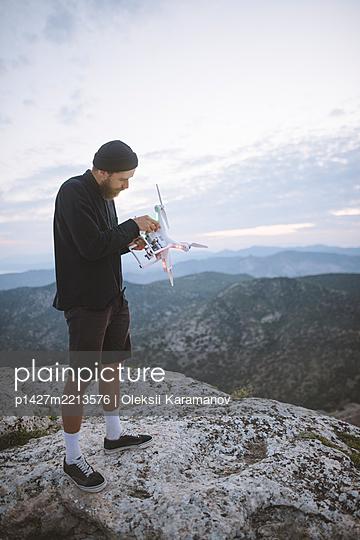 Italy, Liguria, La Spezia, Man at mountain top holding drone - p1427m2213576 by Oleksii Karamanov