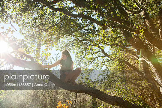 Young woman climbing in tree - p956m1136857 by Anna Quinn
