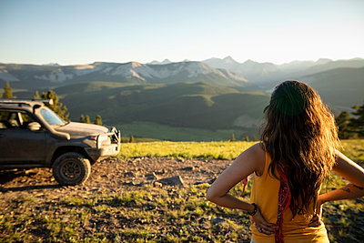 Woman looking at sunny mountain view near SUV, Alberta, Canada - p1192m2016575 by Hero Images