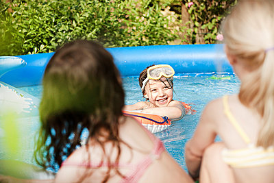 Mädchen im Pool schaut zu Freundinen - p1230m1041788 von tommenz