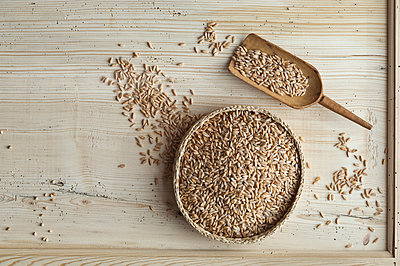 Organic spelt wheat in bast bowl, on wood, from above - p300m2102893 by Achim Sass