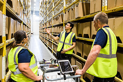 Young worker discussing with coworkers with cart while standing on aisle amidst racks at distribution warehouse - p426m2018860 by Maskot