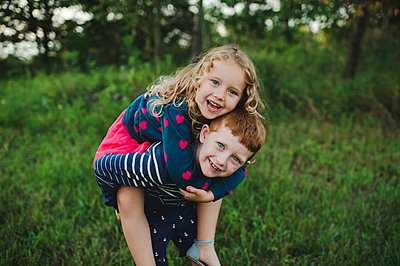 Portrait of boy giving sister a piggyback in field - p429m1504623 by Erin Lester