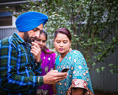 Family in traditional Indian clothing using cell phone - p555m1311800 by Donald Iain Smith