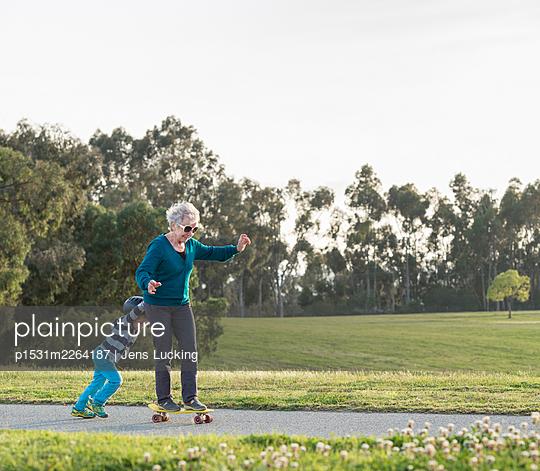 Boy pushing grandmother on skateboard - p1531m2264187 by Jens Lucking