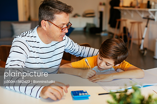 Father watching son doing homework at table - p300m1562423 by Bonninstudio