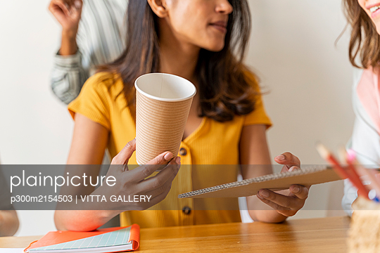 Businesswomen having a meeting in office working on reusable cups - p300m2154503 by VITTA GALLERY