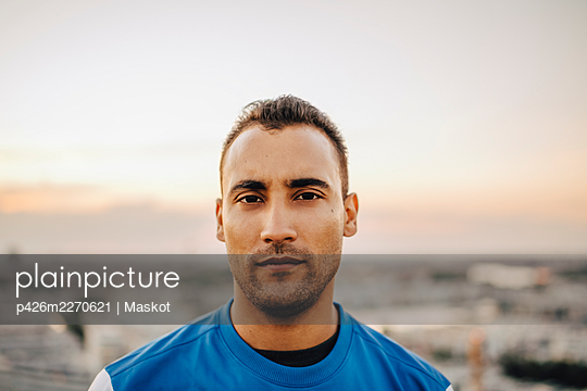 Portrait of confident male athlete against sky during sunset - p426m2270621 by Maskot