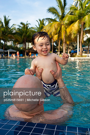 Father and son in the swimming po - p535m815691 by Michelle Gibson