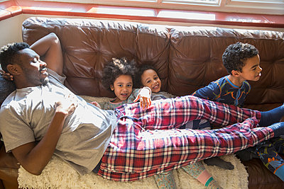 Portrait happy, carefree kids in pajamas cuddling with father on living room sofa - p1023m2016646 by Sam Edwards