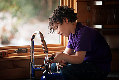 Boy filling water in kettle while sitting at kitchen counter - p1166m1036456f by Cavan Images