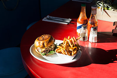 Burger and French fries served in plate on table - p1166m1152100 by Cavan Images