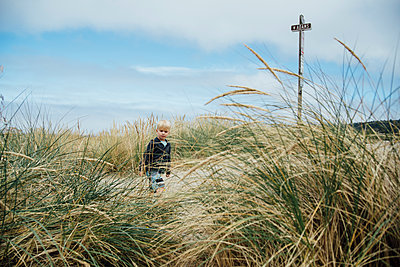 Boy walking by plants at beach against sky - p1166m1524542 by Cavan Images