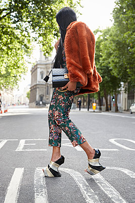 Full length woman in faux fur, silk trousers and high heels - p1407m1545375 by Guerrilla