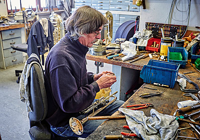 Instrument maker repairing trumpet in workshop - p300m1157042 by Dirk Kittelberger