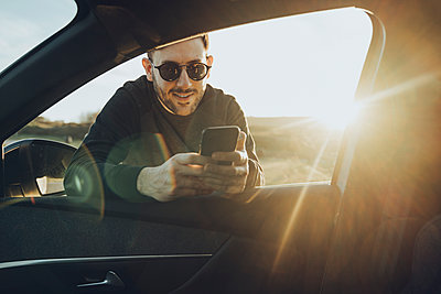 Handsome young man using smart phone while leaning on car window during sunset - p300m2241473 by Mikel Taboada